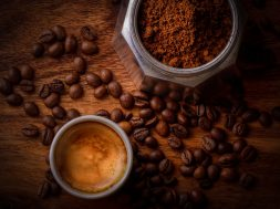 white-ceramic-mug-filled-with-coffee-beside-coffee-beans-678654