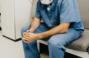 man-wearing-blue-scrub-suit-and-mask-sitting-on-bench-3279197